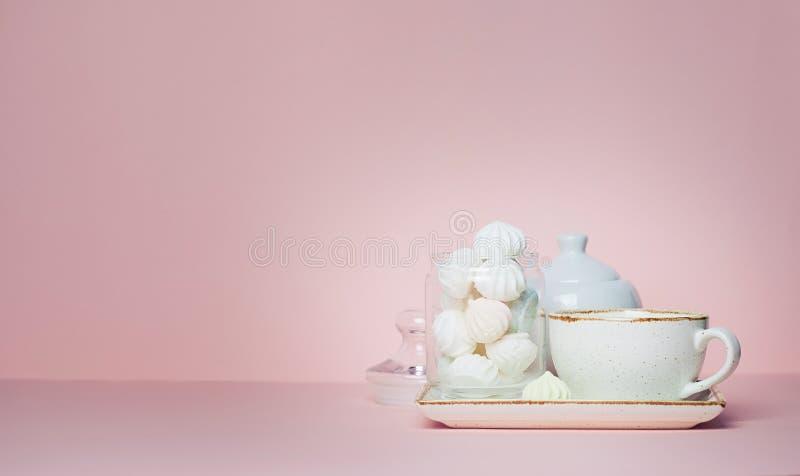 Förlöjliga upp av kopp te och marängar på rosa bakgrund royaltyfria bilder