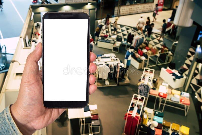 Förlöjliga upp smartphonen för den tomma skärmen i shoppinggalleriabakgrund av b arkivfoton