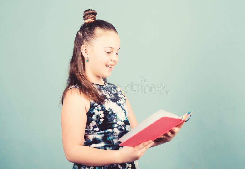 Förlag köksredaktören tittar igenom artikeln liten utgivare skoltidningsreporter liten flicka med anteckning arkivfoto