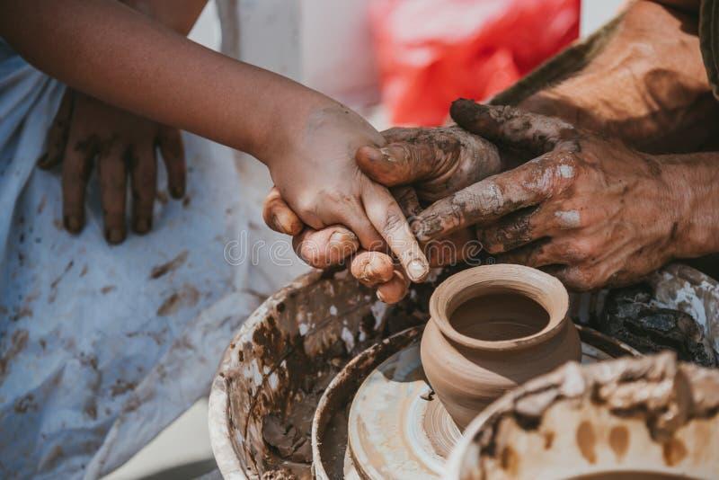 Förlagen av krukmakeri undervisar lite flickan hur man håller fingrar royaltyfria foton