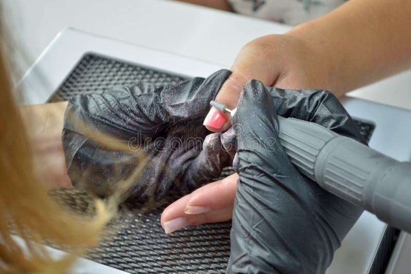 Förlagen av manikyr i svarta handskar tar bort stelnar polermedel med en router arkivfoto