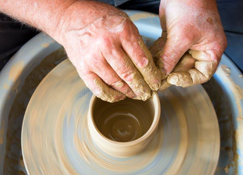 Förlagen bildar en lerakopp på keramikers hjul fotografering för bildbyråer