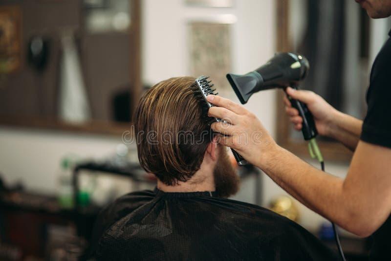 Förlagen klipper hår och skägget av män i frisersalongen och använder en hårtork royaltyfria bilder