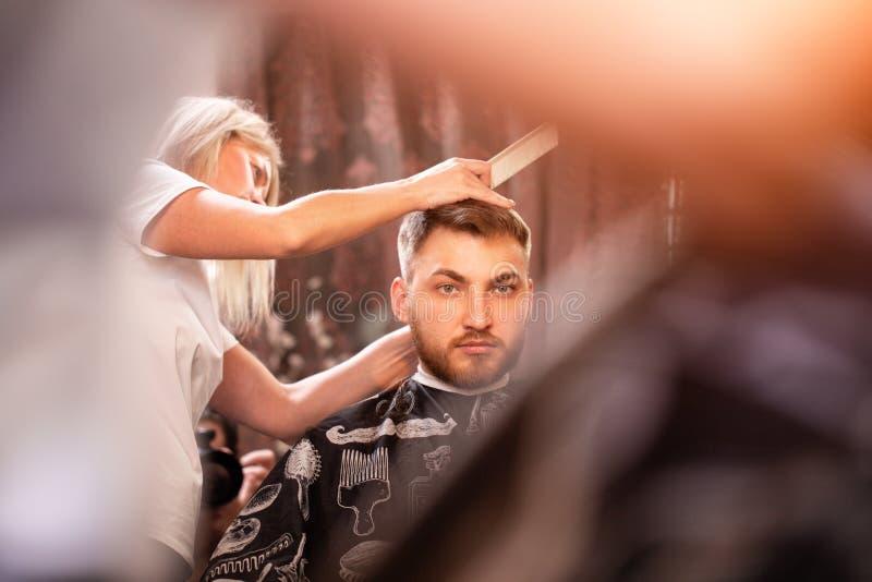 Förlagen klipper håret, och skägget av en man i en frisersalong, en frisör gör en frisyr för en ung man _ arkivfoto