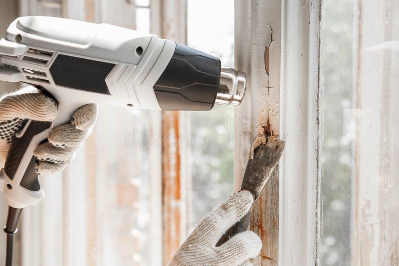Förlagen tar bort gammal målarfärg från fönster med den värmevapnet och skrapan closeup royaltyfri fotografi