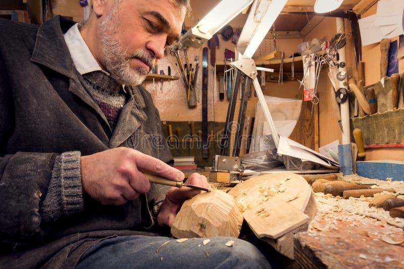 Förlagen undersöker träskulpturer, snickarekontrollerna det färdigt royaltyfria bilder