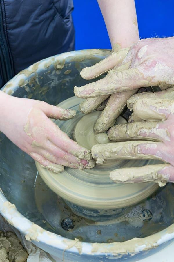 Förlagen undervisar barnet, en student av krukmakeri Hjälp som ska göras ut ur lera på en keramiker` s, rullar en tillbringare arkivbilder