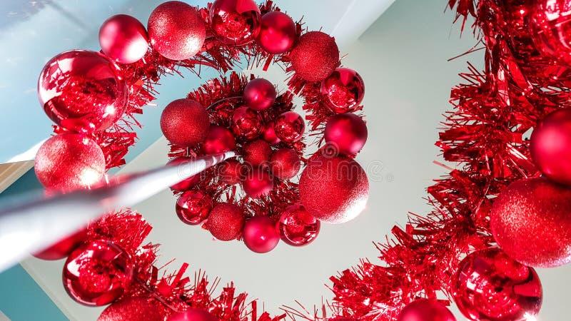 Förlora upp låg vinkel av den moderna formad julgran för metall som spiralen hemma dekoreras med röda temastruntsaker arkivfoton