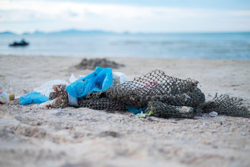 Förlorad avfallförorening på stranden med plastpåsen, netto och flaskan royaltyfri fotografi