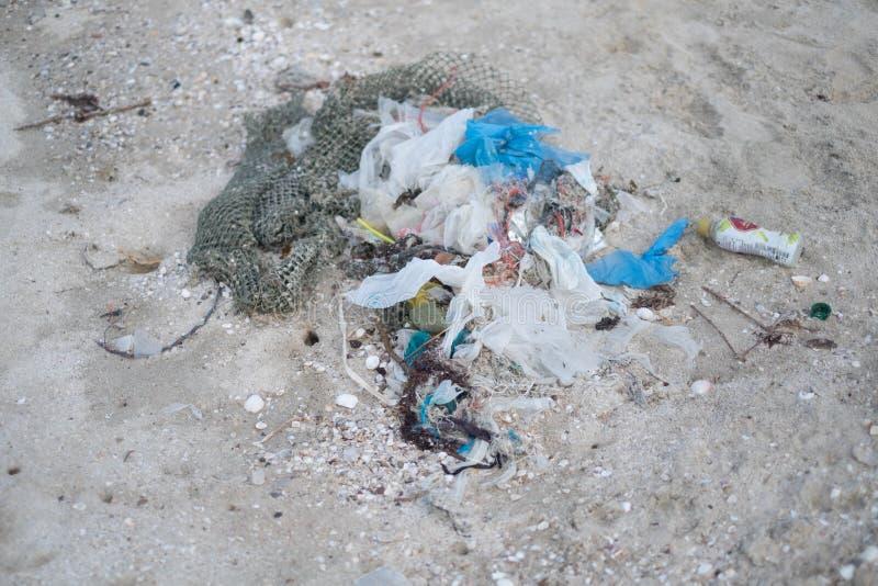 Förlorad avfallförorening på stranden med plastpåsen, netto och flaskan royaltyfri foto