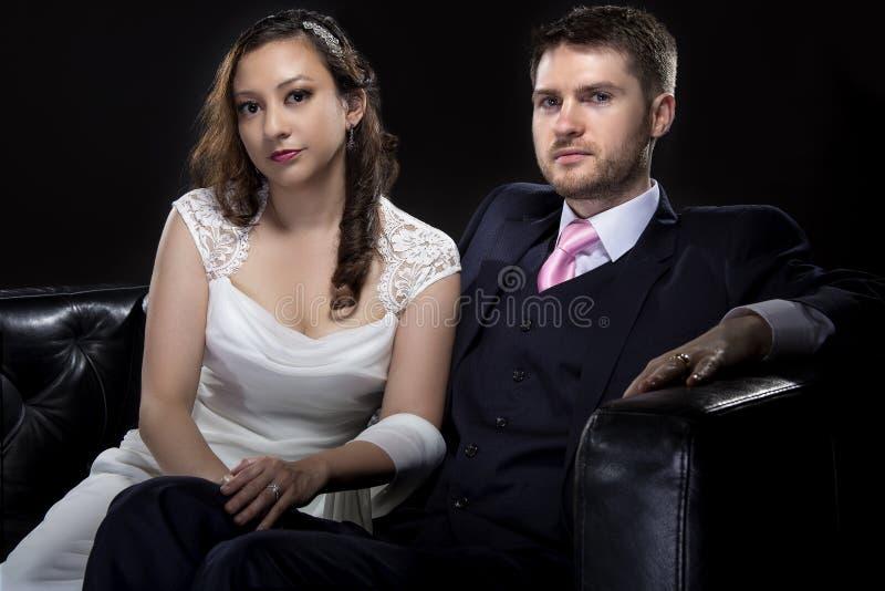 Förlovade par som modellerar Art Deco Style Wedding Suit och klänningen arkivfoto