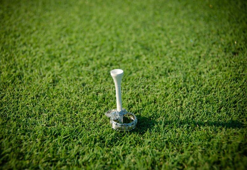 Förlovningsring och vigselring på en golfutslagsplats arkivbild