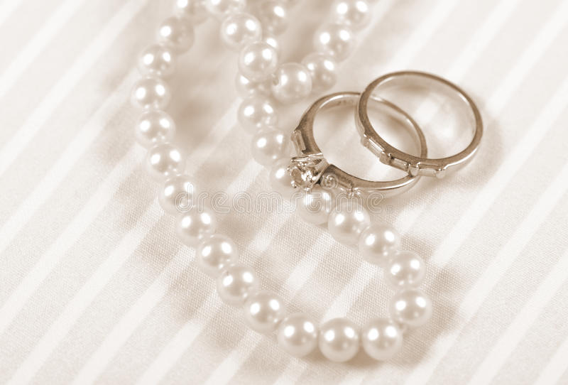 Förlovningsringar för bröllop och för diamant för stil för Sepiatappning retro med den pärlemorfärg halsbandet royaltyfria foton