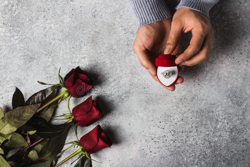 Förlovningsringen för den romantiska handen för mannen för valentindagen att gifta sig den hållande i ask mig bröllop royaltyfri bild