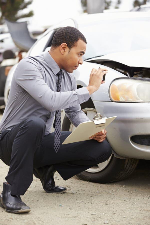 Förlustregulator som tar fotografiet av skada till bilen royaltyfri bild
