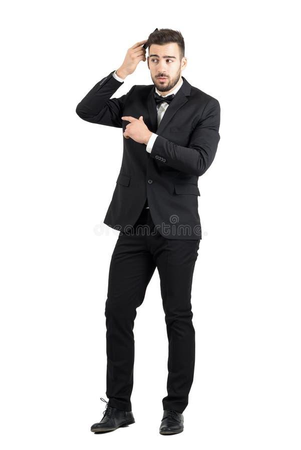 Förmögen lyxig man för skäggstubb som kammar hans hår som bort ser fotografering för bildbyråer