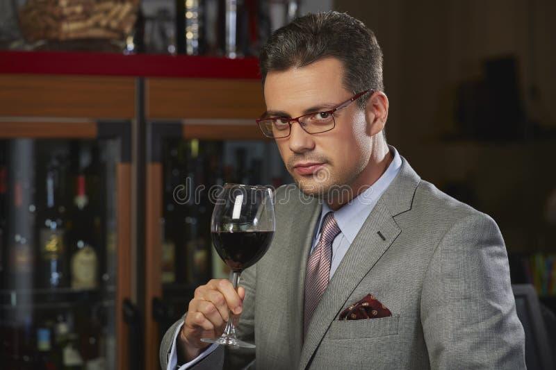 Förmögen man som rostar med vin arkivfoto