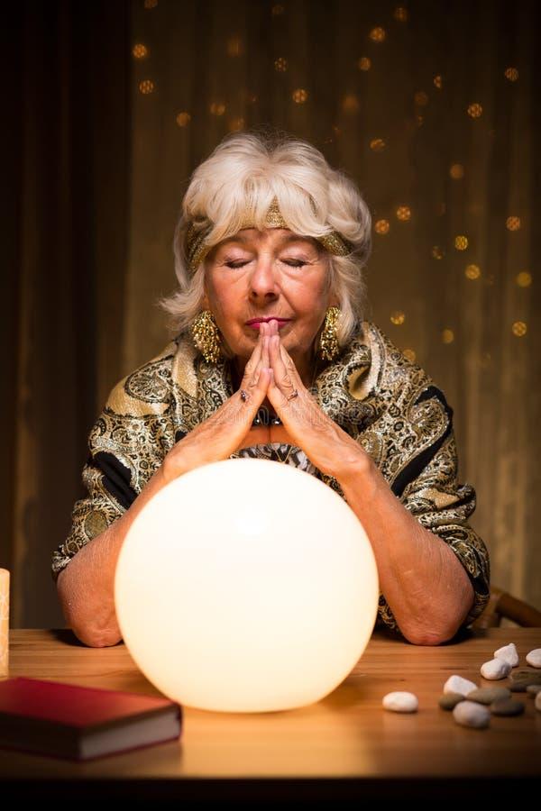 Förmögenhetkassör som använder den magiska bollen fotografering för bildbyråer