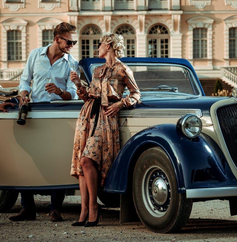 Förmögna par near den klassiska cabrioleten mot kunglig slott arkivbild