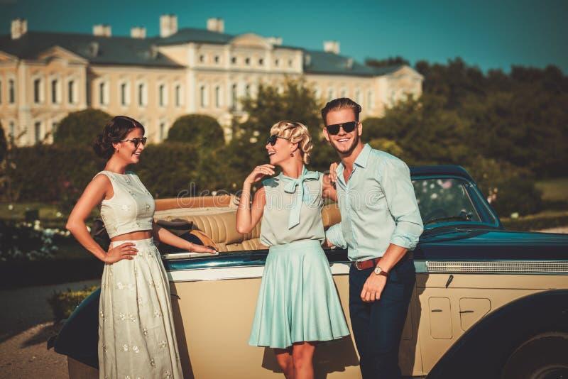 Förmögna vänner near den klassiska cabrioleten royaltyfria foton