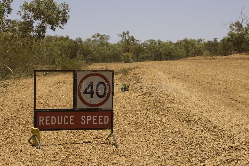 Förminska hastighetstecknet på en öde elasticitet av vägarbeten i vildmark Queensland, Australien royaltyfria bilder