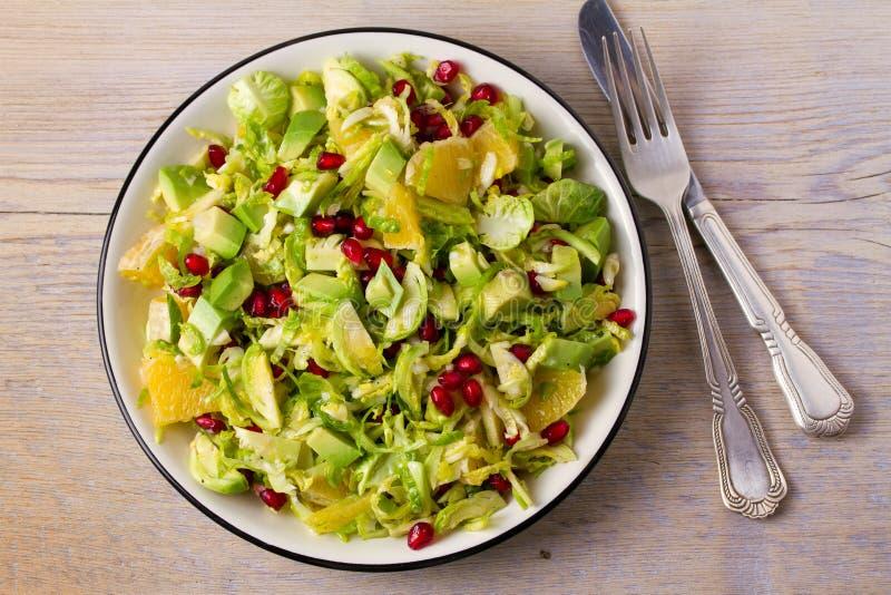 Förnyande Bryssel groddar granatäpple, avokado och orange sallad arkivbild