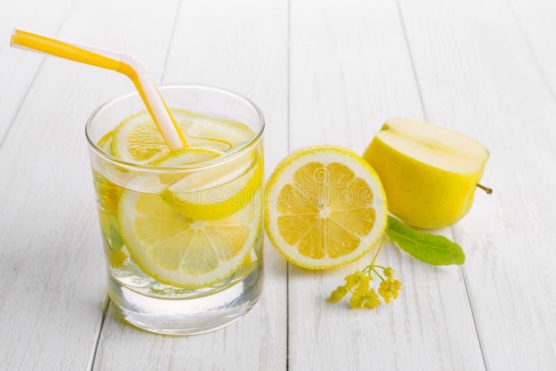 Förnyande drink för detoxification, citronvatten i ett exponeringsglas, nytt äpple och gula lindblommor på en vit tabell arkivfoto