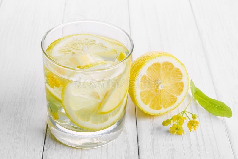 Förnyande drink för hälsa, citronvatten i ett exponeringsglas och gula lindblommor på en vit tabell fotografering för bildbyråer