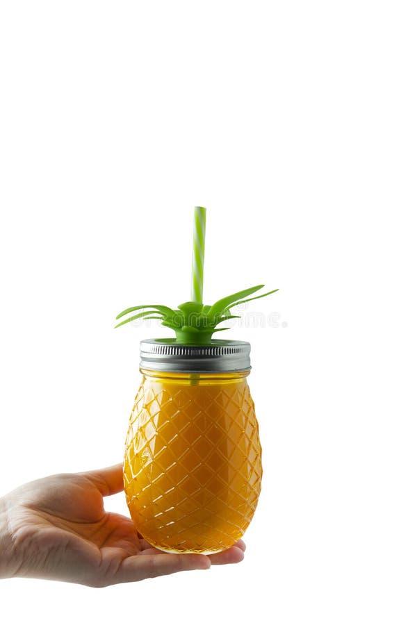 Förnyande drink, fruktsaft eller coctail för sommar Woman' s-hand som rymmer ananasmurarekruset fylld med orange fruktsaft s arkivbilder
