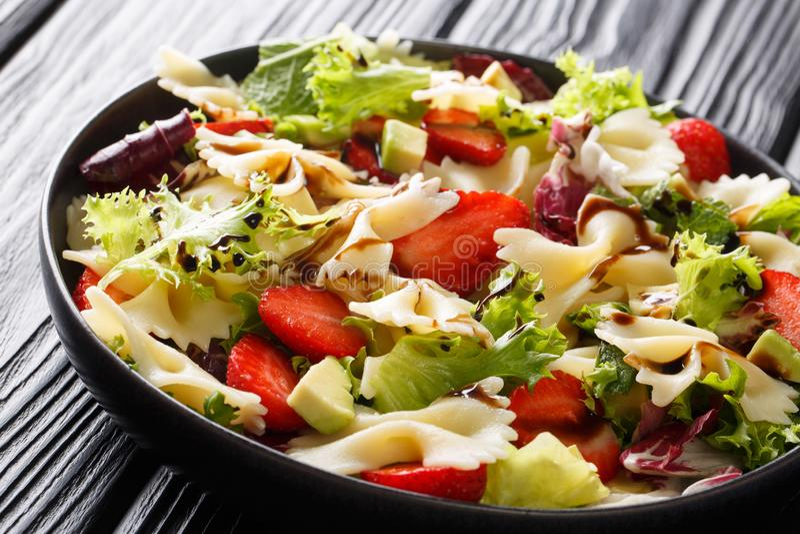 Förnyande farfalle för pastasallad med avokadot, jordgubbar, grönsallat och balsamic såsnärbild horisontal royaltyfri bild