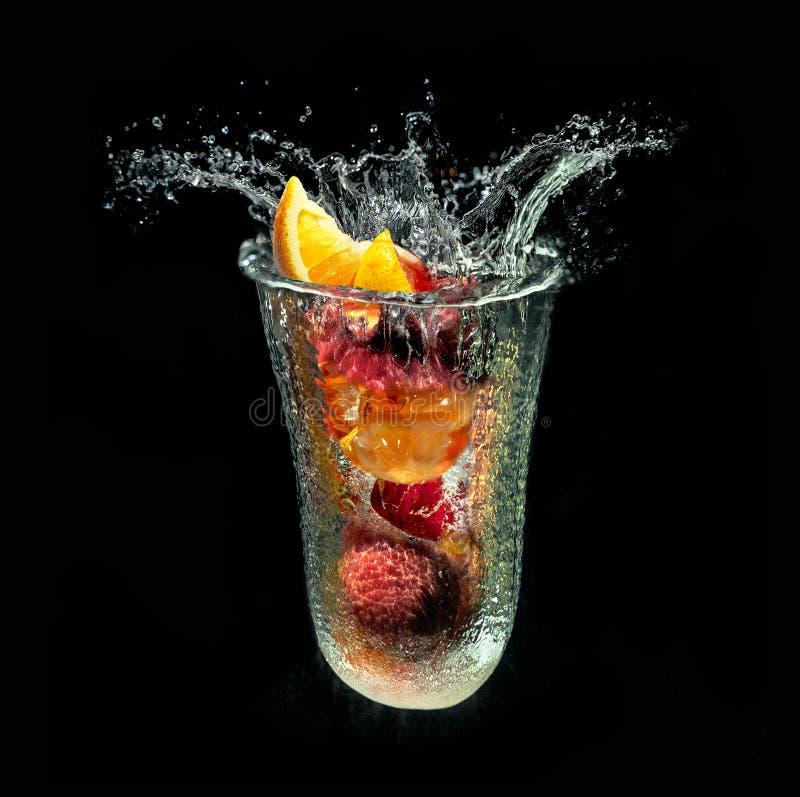 Förnyande fruktefterrätt i imaginärt exponeringsglas ut ur vattenfärgstänk på svart bakgrund arkivfoton