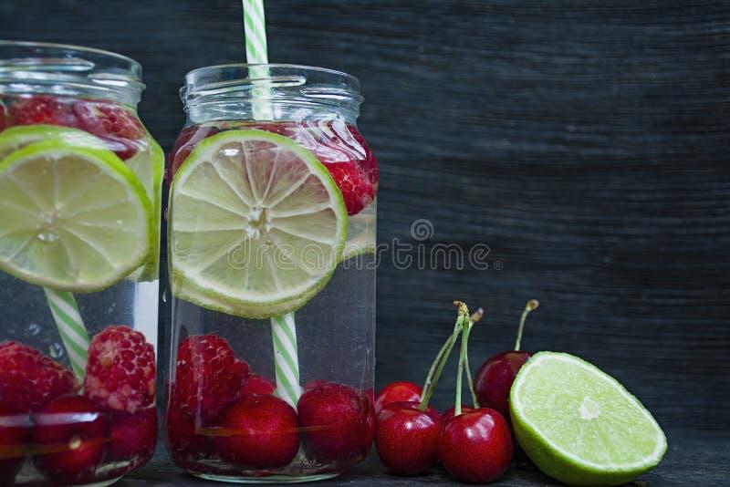 Förnyande sommardrink med frukt Drink som göras från körsbäret, hallon, limefrukt m?rkt tr? f?r bakgrund Utrymme f?r text arkivbild