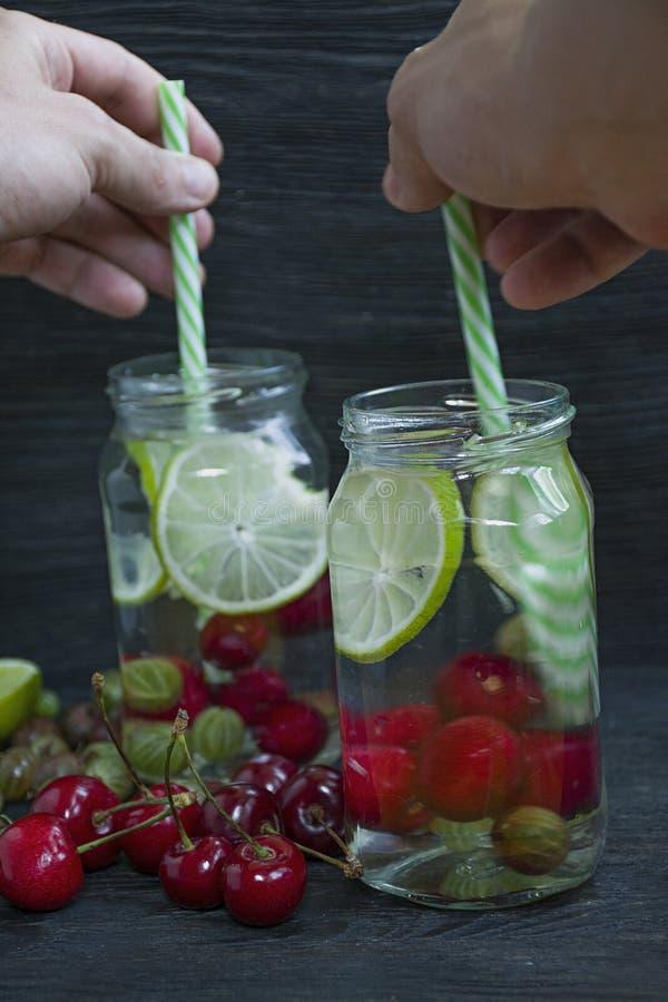 Förnyande sommardrink med frukt Drink som göras från körsbäret, krusbär, limefrukt m?rkt tr? f?r bakgrund royaltyfri foto