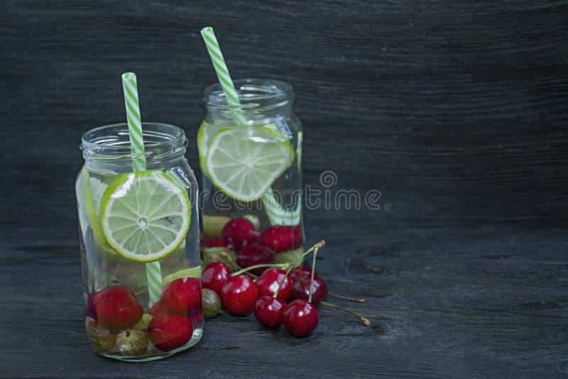 Förnyande sommardrink med frukt Drink som göras från körsbäret, krusbär, limefrukt m?rkt tr? f?r bakgrund Utrymme f?r text royaltyfria bilder