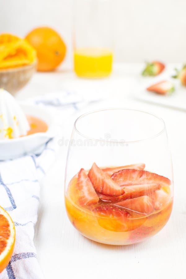 Förnyande sommardrink, sunt mellanmål - nya jordgubbar med orange fruktsaft, metallkorg med jordgubbar, apelsiner royaltyfri foto