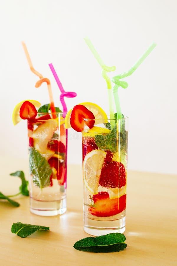Förnyande vibrerande sommardrinkar med citronen, jordgubben och mintkaramellen på trätabellen royaltyfri fotografi