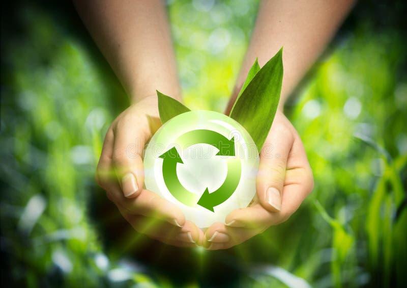Förnybara energikällor i händerna arkivbilder