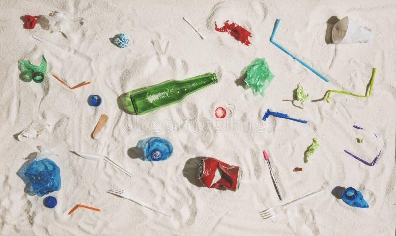 Förorenad strand med plast- och exponeringsglasavfalls arkivfoto