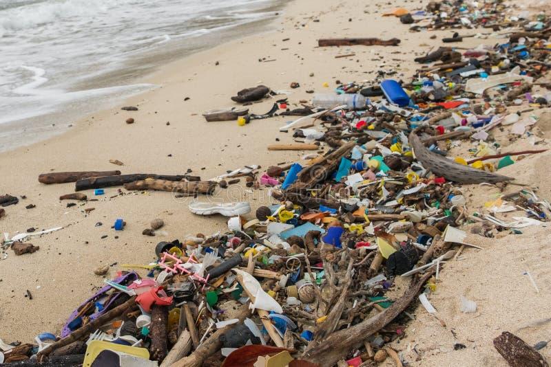 Förorenad strand - plast-avfalls, avfall och avskrädecloseup arkivbild