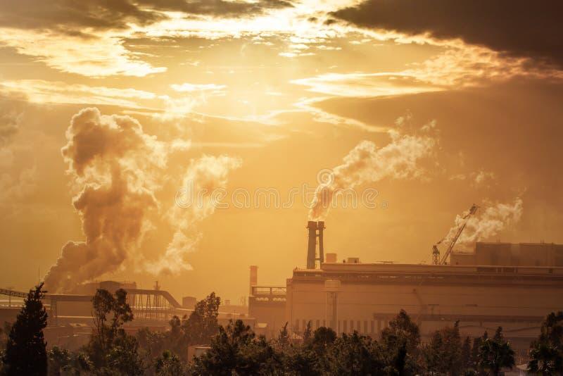 Förorening av miljön av tung bransch Industriellt landskap på solnedgånghimmel royaltyfri bild