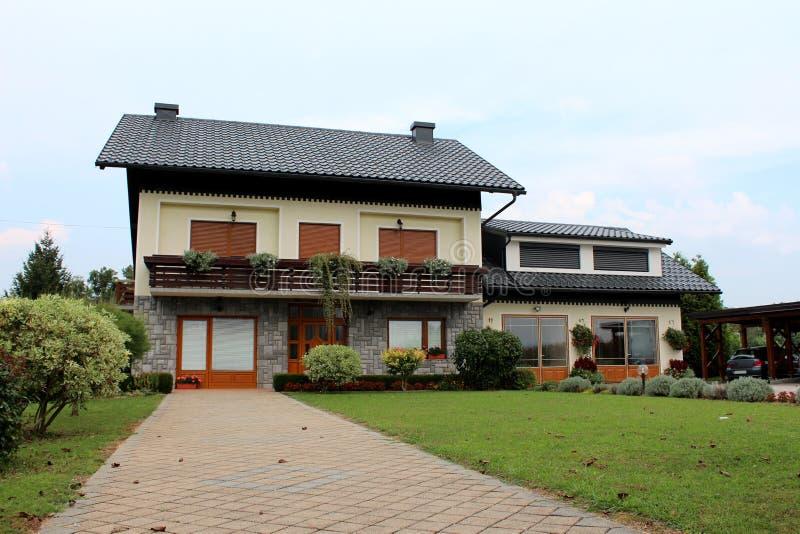Förorts- familjhus med stentegelplattakörbanan och det nya garaget som omges med nytt klippt grönt gräs och små dekorativa träd arkivbilder