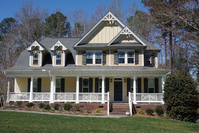 Förorts- hem med en gul yttersida och en stor farstubro arkivbilder