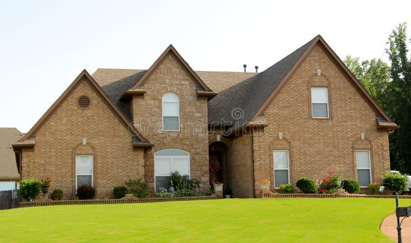 Förorts- hem med härlig texturerad kullersten och färgrika bruna tegelstenar royaltyfri bild