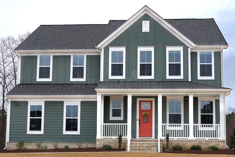 Förorts- hem- yttersida med en röd dörr i en grannskap i North Carolina arkivfoto