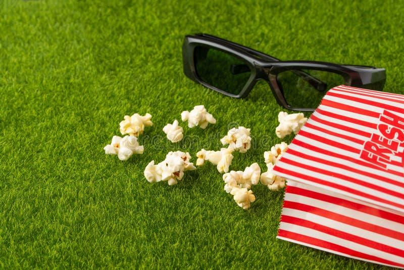 Förpackning med popcorn på en grön gräs med 3D-glas för att titta på film. Grass Watching filmer om naturen. I parker. rekre royaltyfri fotografi