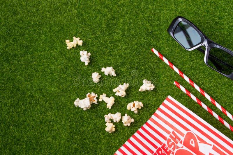 Förpackning med popcorn-strålar för soda på en grön gräs med 3D-glasögon för att titta på film Grass Watching filmer om naturen I royaltyfri bild
