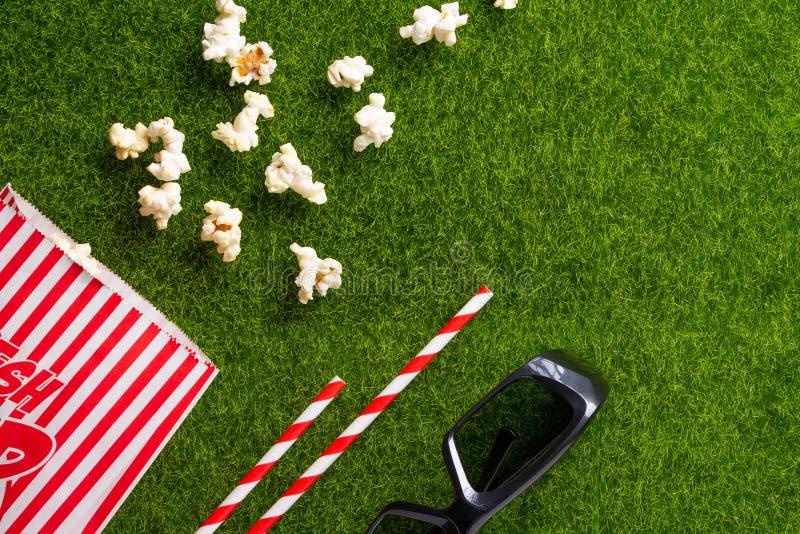 Förpackning med popcorn-strålar för soda på en grön gräs med 3D-glasögon för filmvisning. Grass Watching filmer om naturen royaltyfri foto