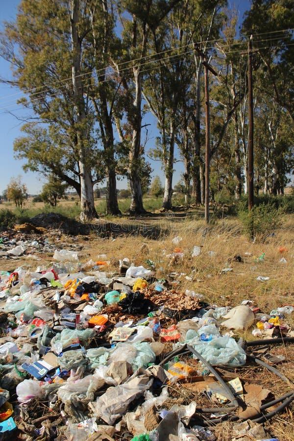 Förrådsplatsen med olik typ av avfall, det främst plast- hushållet rackar ner på i en äng nära Bloemfontein i Sydafrika arkivfoto