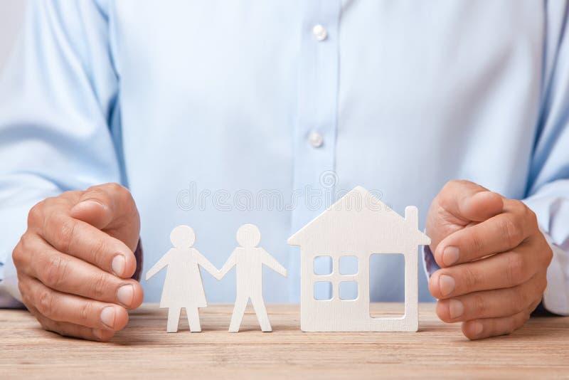 Försäkring av en ungt familj och hus Mannen i skjorta täcker hans händer med par av två män royaltyfria foton