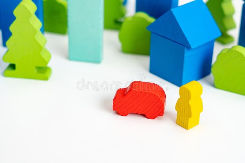 Försäkring eller affärsidé Träperson med en bil på gatan arkivbild